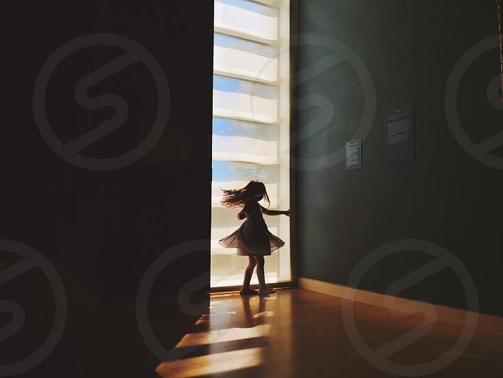 girl standing near window photo