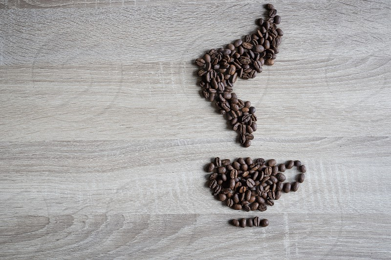 Flat lay of  coffee beans in form of coffee pouring from a sack to a cup shape on wooden background. Creative minimal concept photo