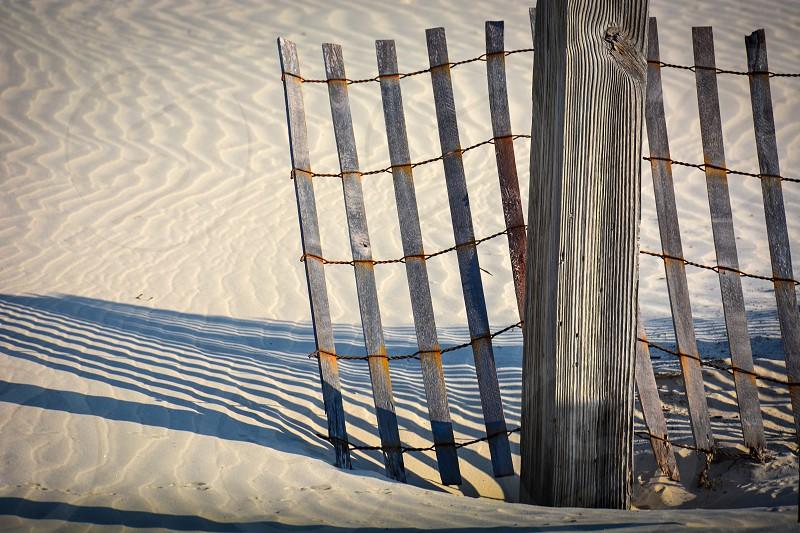 sand dunes ripples shadows fence wood rusty weathered beach photo
