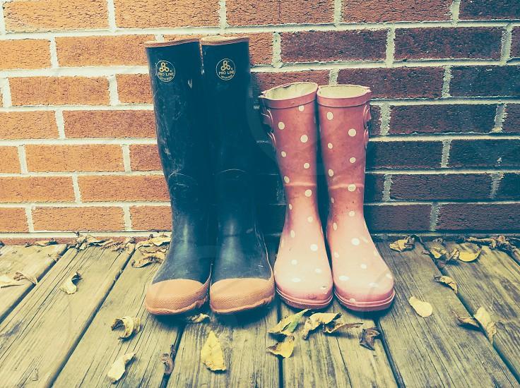 black rubber rain boots beside red and white polka dot rain boots photo