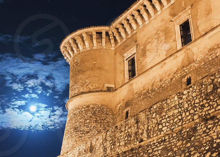 night view of the Alviano medieval castle in Italy with clouds and glowing moon photo