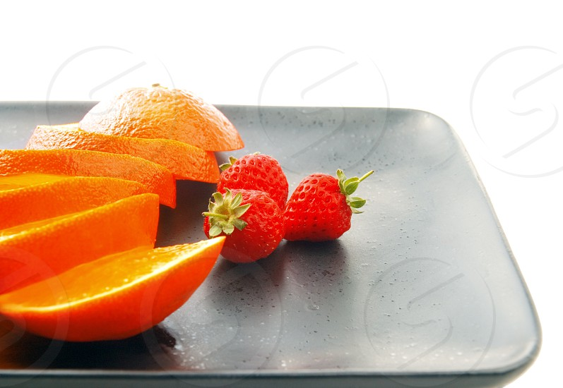 orange & strawberries on a plate on white background photo