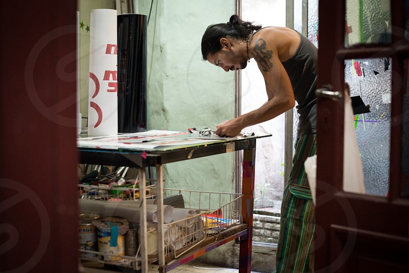 Latin American adult man working passionately and concentrated with his hands and colors photo