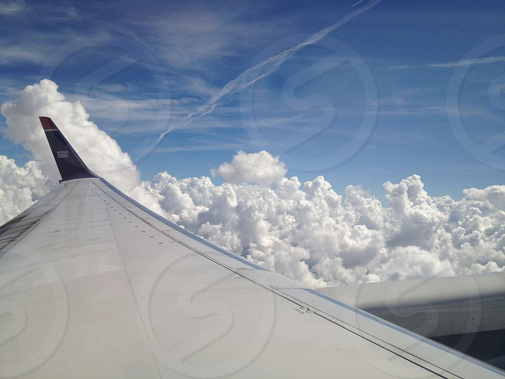 silver airplane wing across white cumulus clouds photo