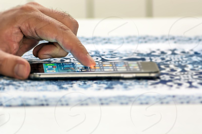Man hand touching screen on modern smart phone on a decorated table cloth. Close-up image with shallow depth of field focus on finger. photo