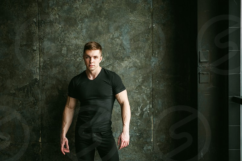 Young sexy men bodybuilder athlete studio portrait loft on background of stylized Concrete brutal wall guy model black Tshirt and trousers With powerful muscular arms photo