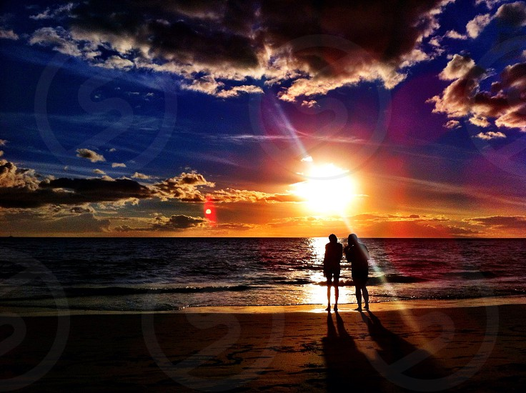 2 person watching the orange sunset in the seashore photo