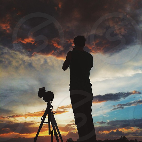 man with a camera at sunset photo