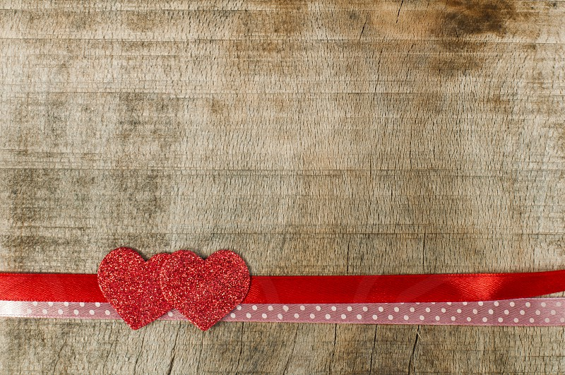 Red ribbon tape and hearts on wooden background. photo