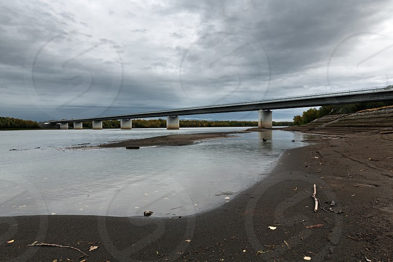 Modern highway bridge over Kamchatka River is largest longest and most flooded river on Kamchatka Peninsula. View of bridge in cloudy weather. Eurasia Russian Far East Kamchatka Region. photo
