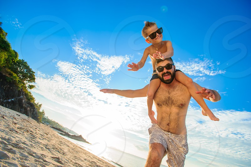 Eight years old boy sitting on dad's shoulders. Both in swimming shorts and sunglasses having fun on the beach. Bottom view. Blue sky and altocumulus clouds behind them photo