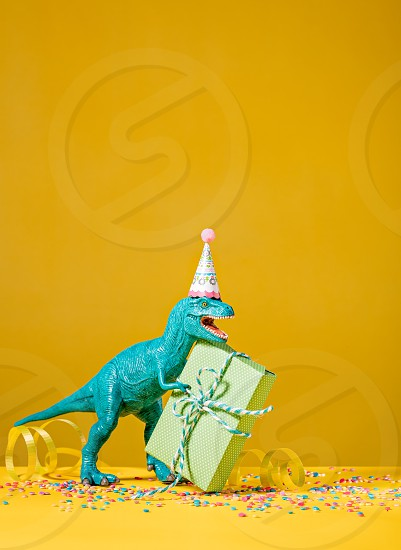 Toy dinosaur with birthday gift wearing a party hat on a yellow background. photo