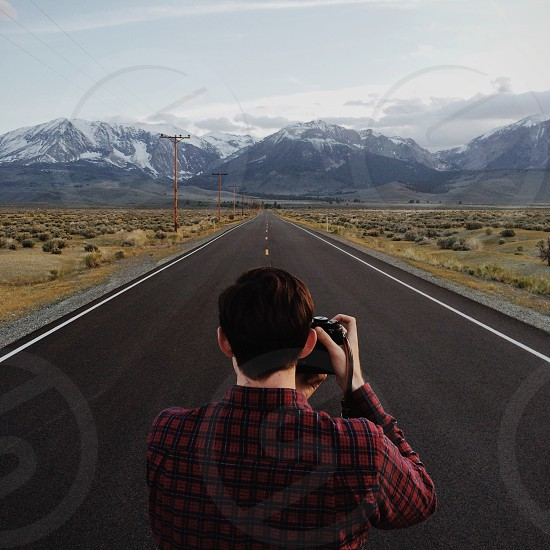 man in black and red checkered button down shirt taking picture in the middle of the road photo