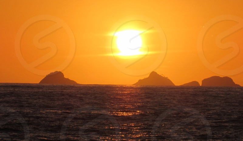 golden yellow sunlight over silhouette of islands in sea water photo
