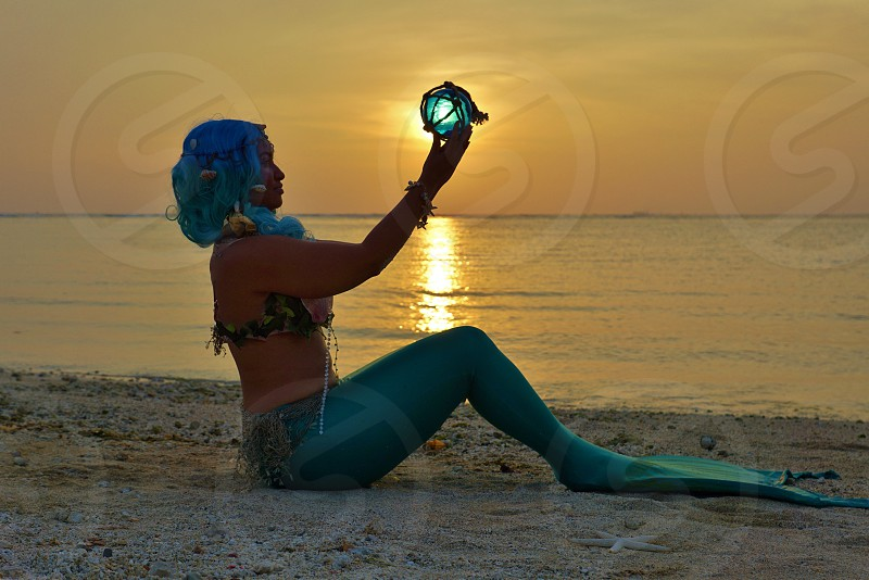 woman with mermaid costume holding blue ball near beach photo