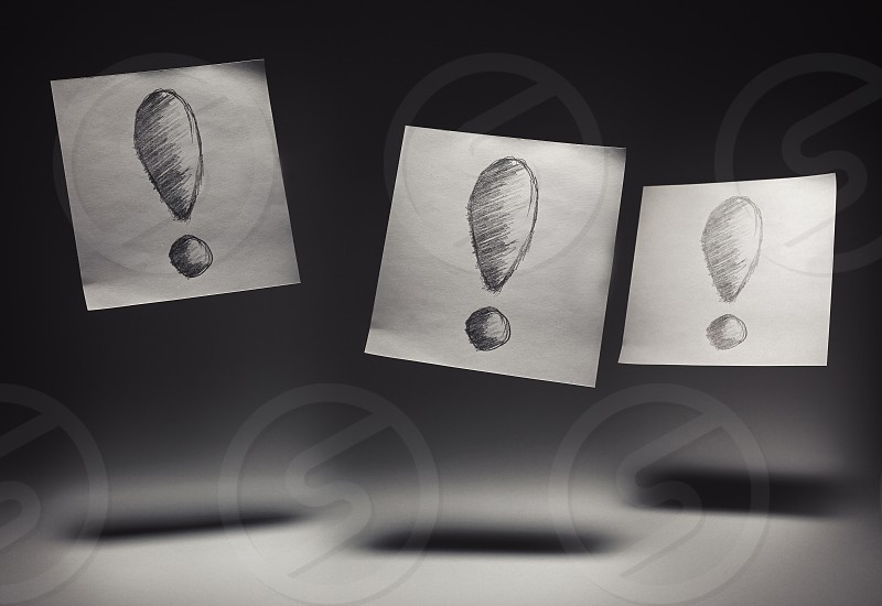 Exclamation marks drawn on paper on gray background.  photo