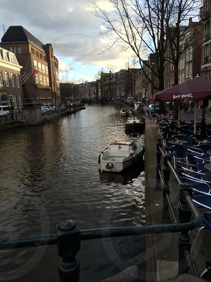 tables and chairs near canal in amsterdam photo