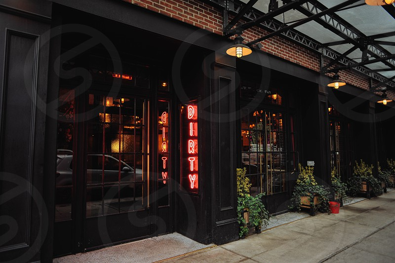 dirty french nyc restaurant front with black wood framed windows on a brick building photo