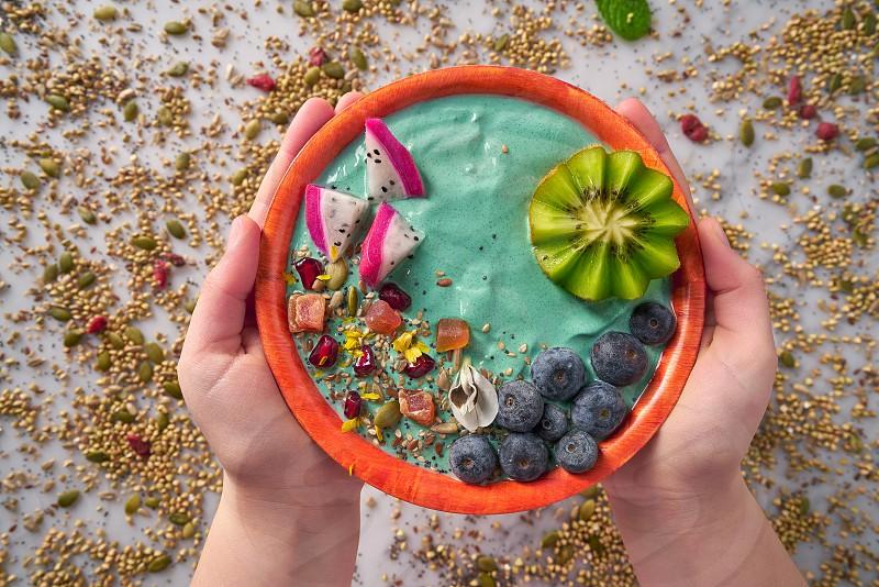 Acai bowl smoothie with kiwi blueberry seeds and pitaya dragon fruit photo