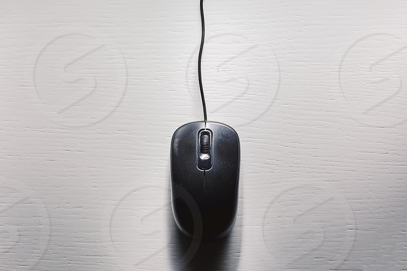 Old dusty black computer mouse on white table.  photo