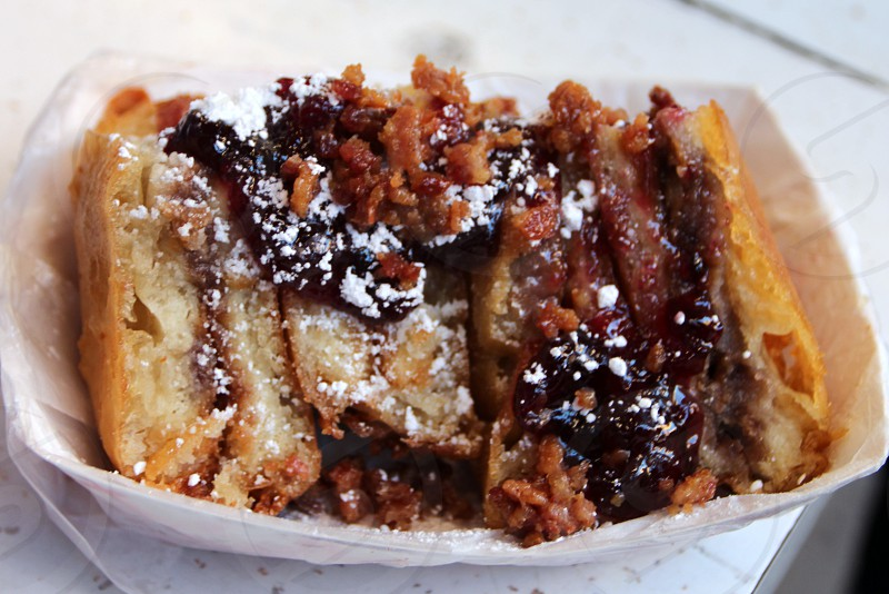Deep fried peanut butter and banana sandwich with strawberry jam powdered sugar and bacon  state fair food photo
