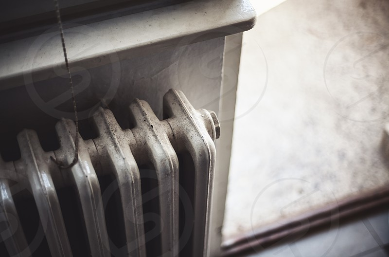 Details of an old radiator and part of a terrace in blurry background. photo