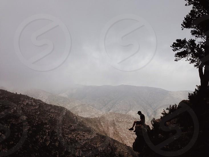 man in black t shirt sitting on rock photo