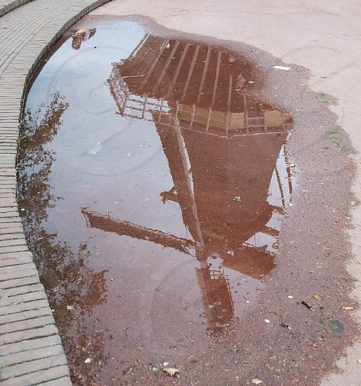 puddle of water at side of concrete road with reflection of windmill and trees at daytime photo