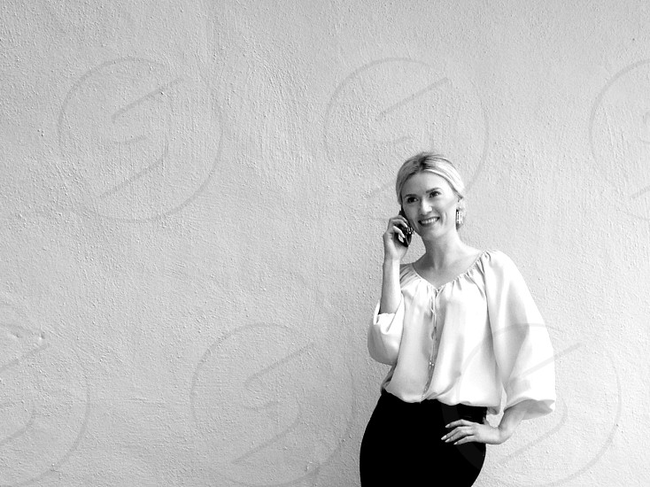 black and white image of woman in white blouse talking on phone near wall photo