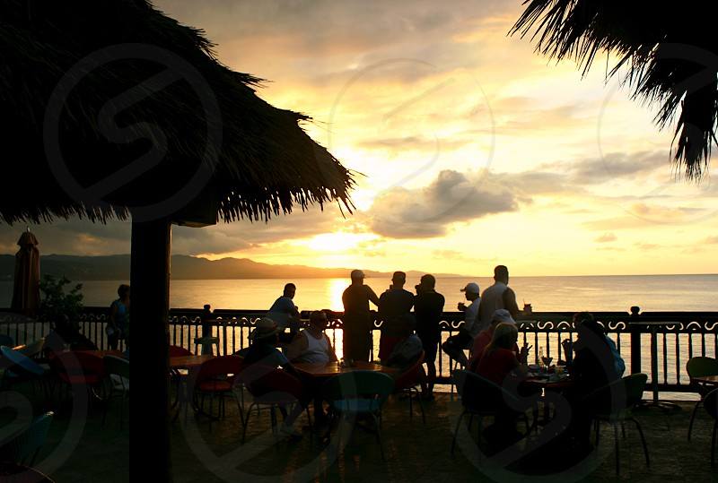 Sunset silhouette party people crowd bar restaurant rooftop roof top drinks dinner fun men woman tropical escape booze alcohol bar island restaurant resort Caribbean travel tourists locals mix music relax relaxing view sunset ocean beach island time balcony porch watching viewing unwind group holiday party chill chilling hanging out guys girls couples romantic scene pictures moment priceless talking socializing photo