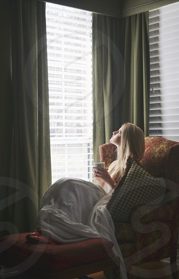 person sitting beside a window photo