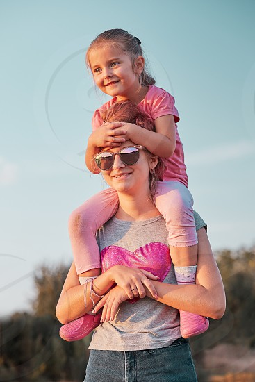 Sisters enjoying piggyback ride. Teenage girl carrying her younger sister up on the back and shoulders spending time playing together outdoors in the countryside. Candid people real moments authentic situations photo