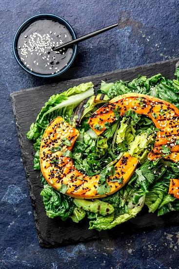 Grilled pumpkin and lettuche salad with white and black sesame and balsamic sauce on slate black board blue stone background. photo