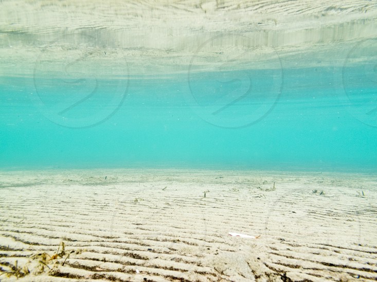 Sandy bottom of shallow blue-green water is mirrored on calm surface photo