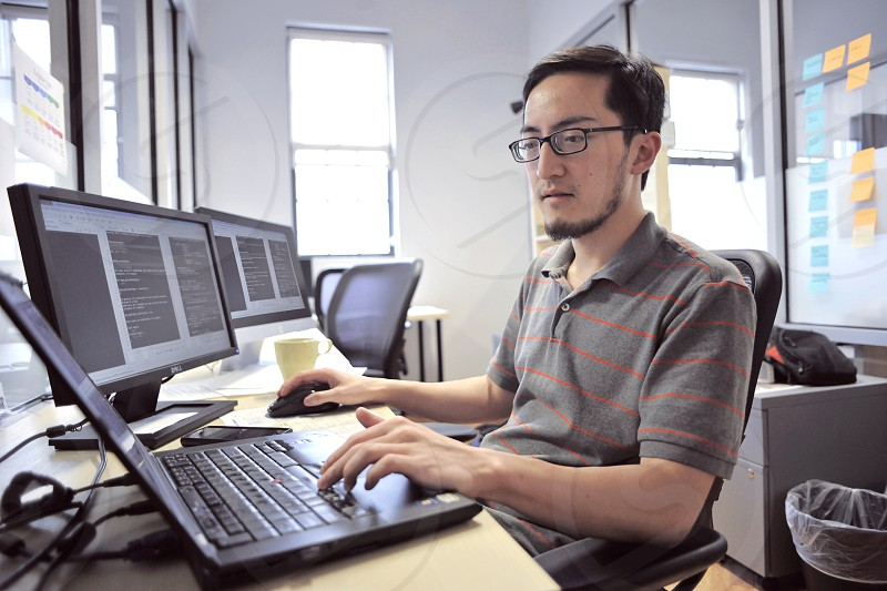 man in grey and red stripe polo shirt using grey laptop computer on desk photo