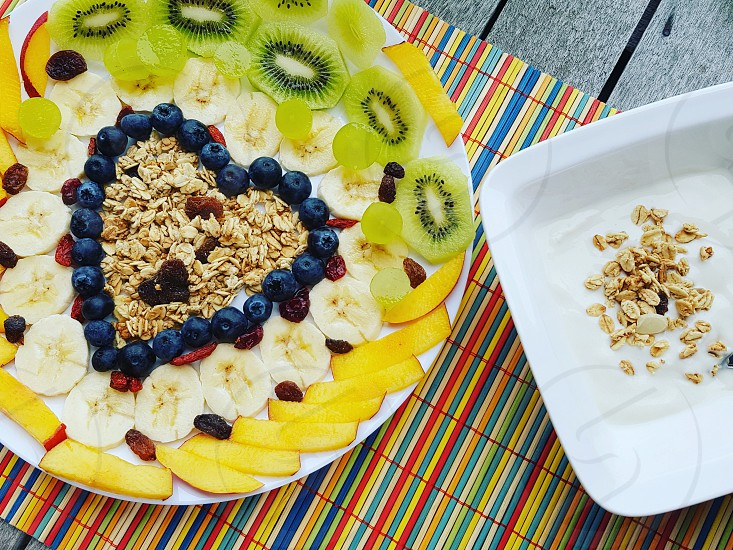healthy breakfastbreaks with granola banana's kiwi blueberries peach goji berries and yogurt on a colurful tablemat photo