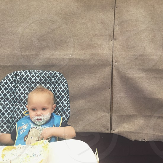 baby in blue and brown bib sitting in high chair covered his/her face with icing photo