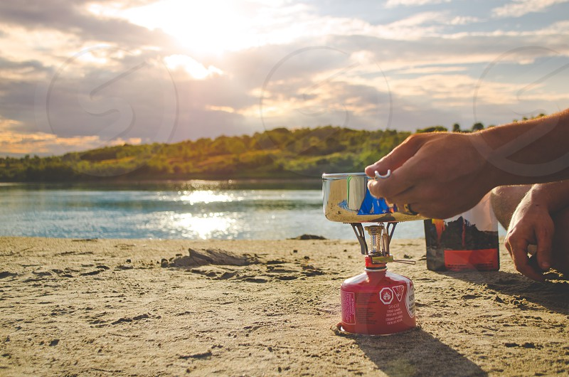 Person cooking outdoors on a campstove in the wilderness. Beach and lake in the background.  photo