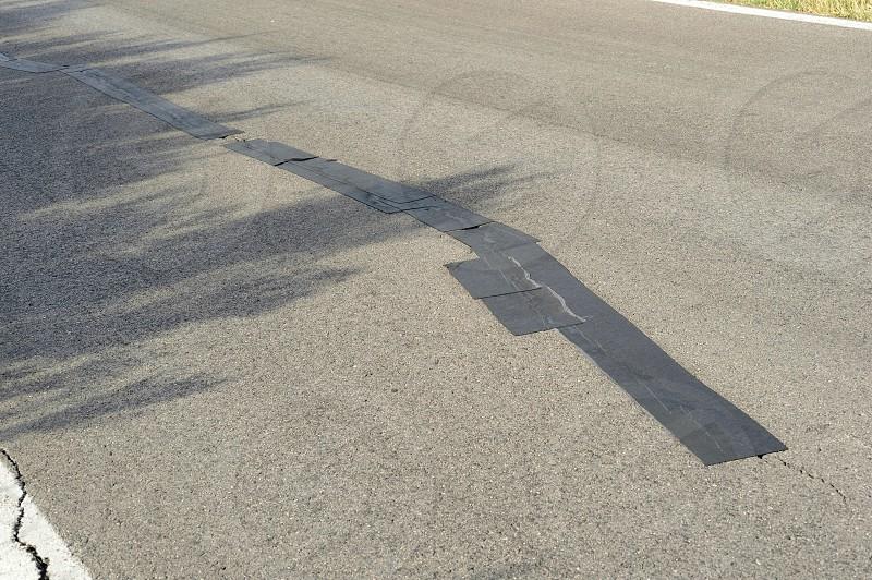 black adhesive tape on road cracks photo