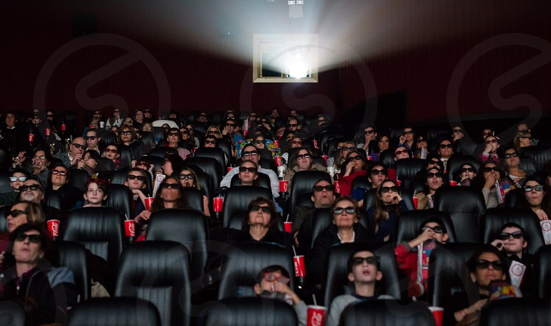 audience of people in movie theater watching 3d movie with 3d glasses and food and drink photo