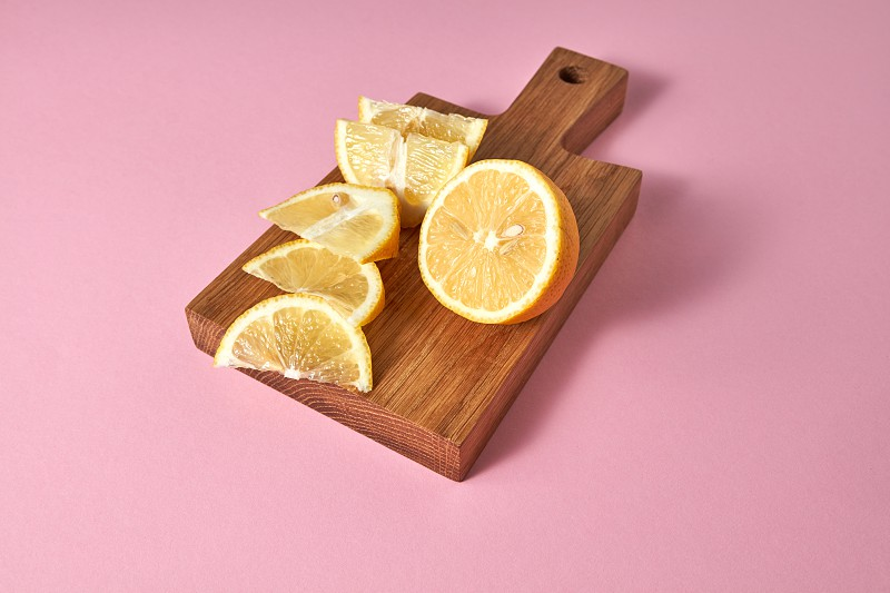 Natural ingredients for preparation natural homemade alcoholic mojito. Slices of natural organic lemon on wooden board on green. Copy space. photo
