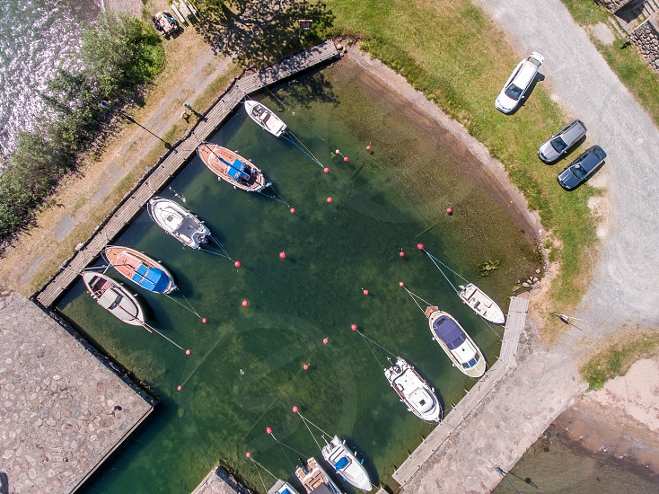 aerial photography of motorboat in green body of water near cars park besides pathway during daytime photo