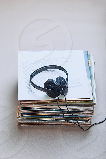 Stack of many black vinyl records headphones on the top of stack. Candid people real moments authentic situations photo