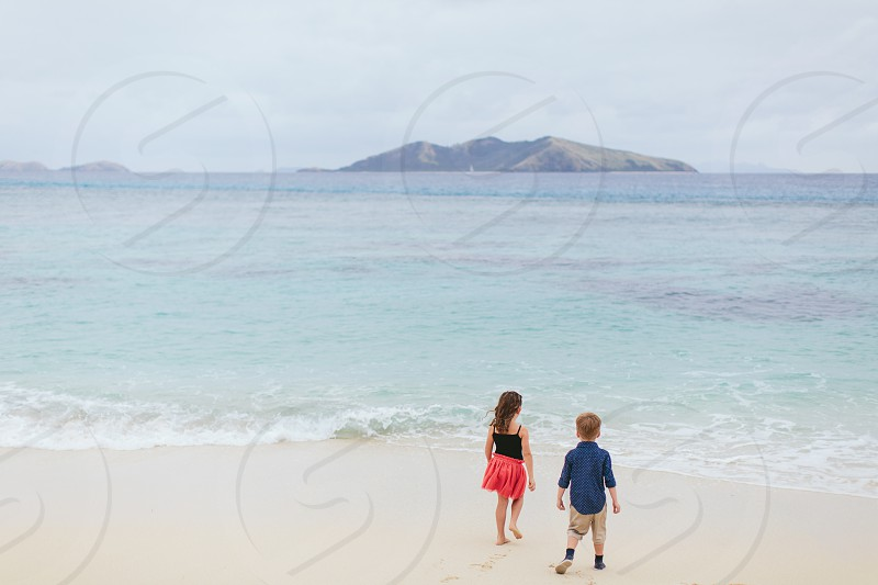 travel family kids toddler kid playing beach ocean water summer adventure holiday girl boy overcast sun blue water sand play photo