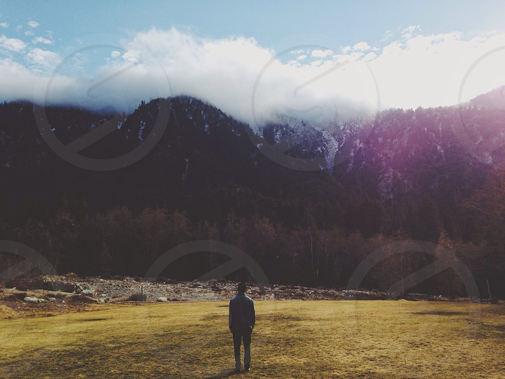 man standing infront mountain photo