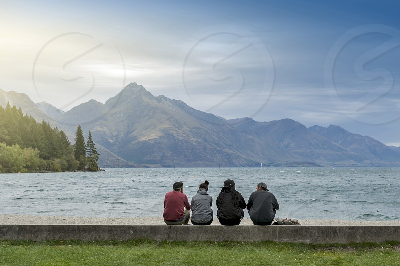 Tourists enjoying spectacular view of Lake Wakatipu at Queenstown lakefront New Zealand photo
