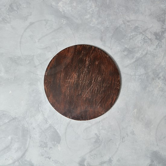 The central composition with brown wooden board on a gray concrete background can be used for display or montage your products photo