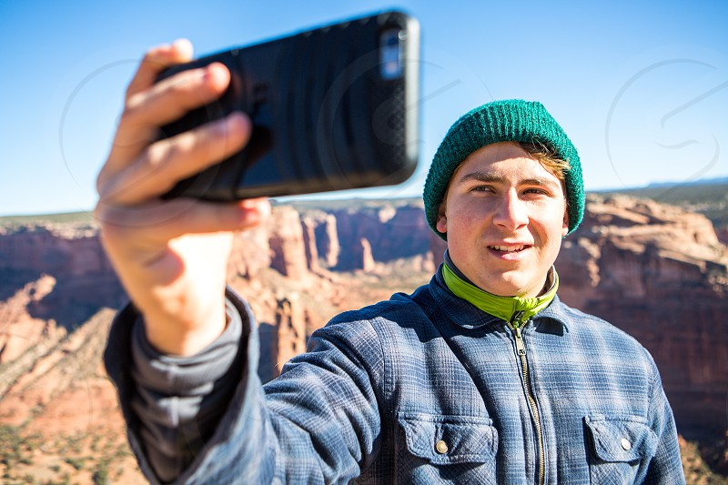 Thanksgiving vacation young man taking a cell phone picture over canyon de chelly national park Arizona photo
