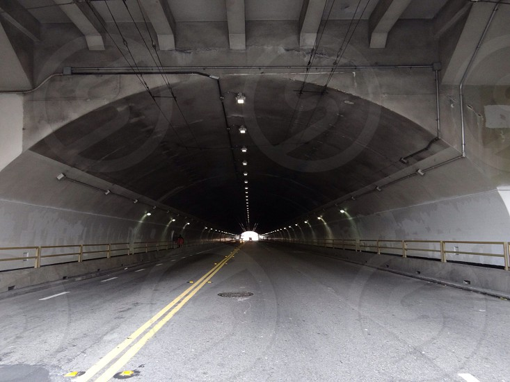 paved roadway under cement tunnel  photo