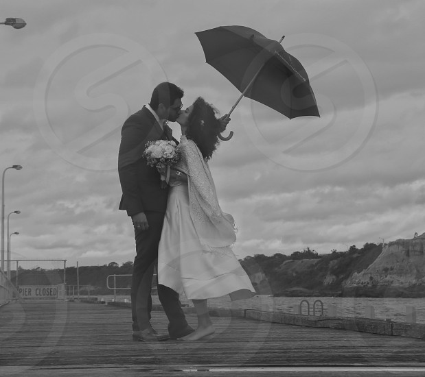 newlyweds standing on a pier photo